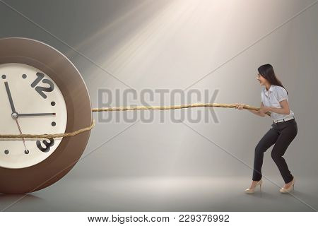 Pretty Asian Businesswoman Pulling A Clock With Rope
