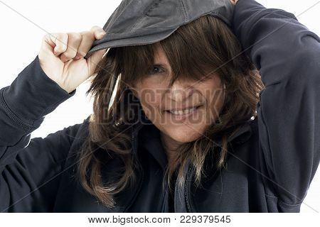 Mature Woman With Brown Hair Putting On A Driving  Cap