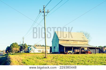 A colorful old farm with a large barn and telephone pole.