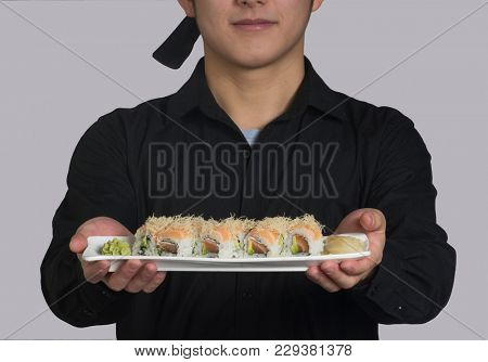 Asian cook hold a sushi roll dish.
