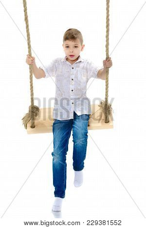 A Cute Little Boy Swinging On A Swing. The Concept Of A Happy Childhood, Healthy Lifestyle. Isolated