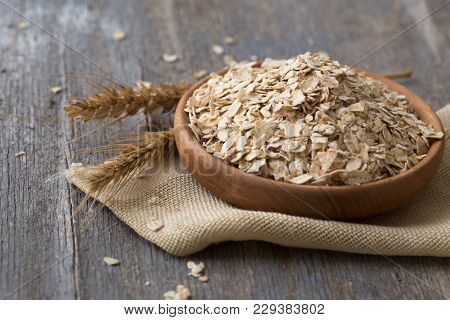 Oat Flakes Or Oatmeal In Wooden Plate On Rustic Wood Table. Rolled Oat Is Clean Food For Health Love