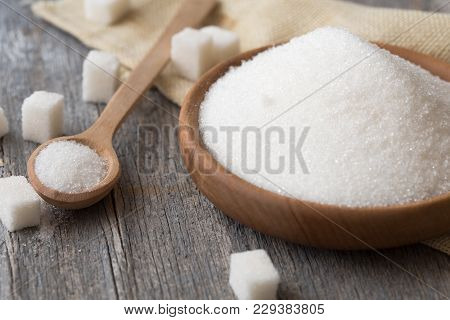 Sugar cubes, granulated sugar in spoon and plate. White sugar on gray galvanized iron background. Copy space. poster