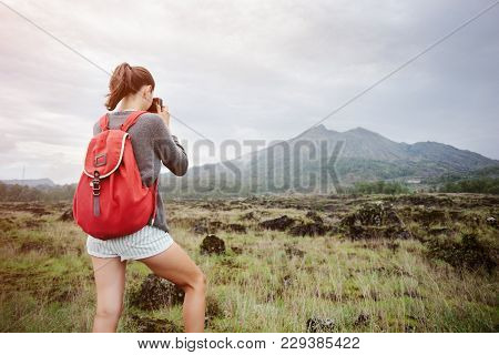 Fit Traveling Girl Taking Photo Of Volcano In The Wild, Intentional Sun Glare And Vintage Color
