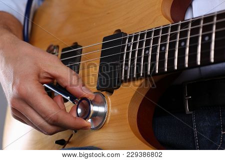 Male Arms Hold Stethoscope Head Fine Diagnosing Classic Shape Wooden Guitar Closeup. Six Stringed Sc