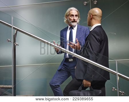 Caucasian And Latino Corporate Executives Having A Conversation While Ascending Stairs In Modern Off