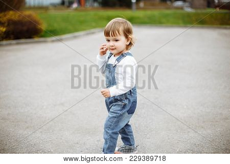 Little Blonde Girl Standing On A Road