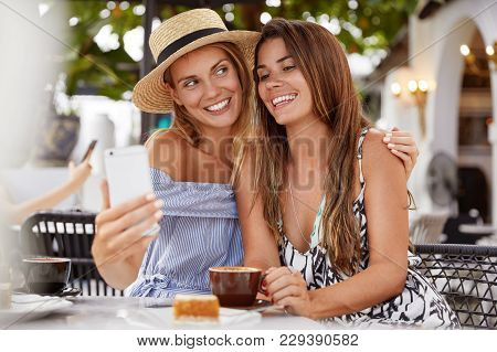 Outdoor Shot Of Homosexual Women Couple Embrace Each Other And Make Photo Of Themself On Mobile Phon