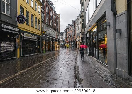 Copenhagen - October 22, 2016:  A Woman With A Red Umbrella, Walking  On A Narrow Street