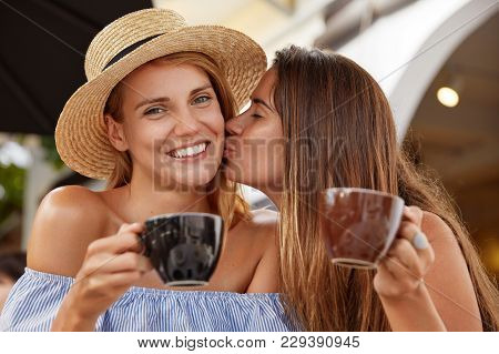 Lovely Couple Of Lesbian Females Drink Coffee At Outdoor Cafeteria, Enjoy Togetherness, Kiss Each Ot