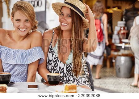 Relaxed Young Female Tourirsts Have Fun Together At Cafeteria, Sit Next To Each Other, Wear Summer C