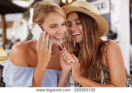 Portrait Of Cheerful Adorable Female Has Mobile Conversation With Friend And Her Jealous Girfriend T