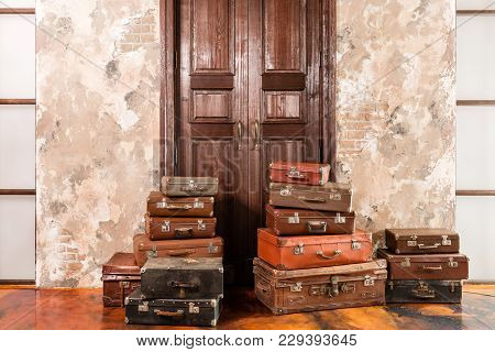 The Door And The Bag. Vintage Used Travel Suitcases. Many Old Vintage Suitcase. Luggage Concept.