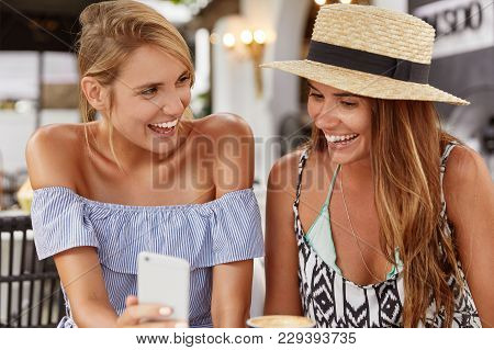 Portrait Of Happy Females Dressed In Stylish Summer Clothing, Laughs Joyfully As Watch Funny Photo O