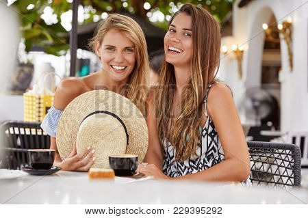 Two Attractive Female Best Friends Happy To Meet Together At Outdoor Cafeteria After Spending Summer