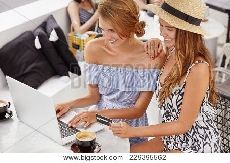Happy Homosexual Female Lesbian Couple Enjoys Free Wifi And Have Fun At Coffee Shop Together, Use Ge