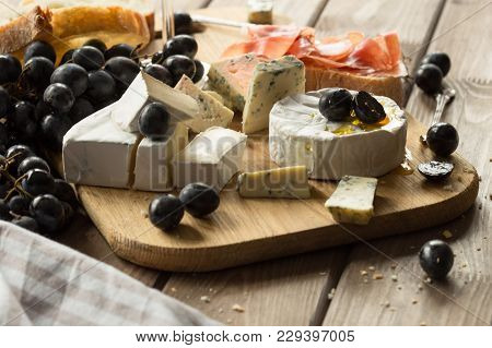 Wooden Board Of Various Types Of Cheese And Garnishes