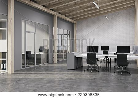 Modern Office Interior With White Brick Walls, A Concrete Floor And Rows Of White Computer Desks. An