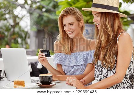 Two Female Lesbians Spend Leisure Time Together At Coffee Shop, Work On Laptop Computer, Make Online