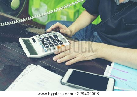 Business Concept : Local Businessman On The Phone And Using Calculator In The Office
