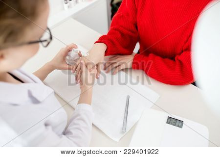 Close-up Shot Of Unrecognizable Young Manicurist Sitting At Table Opposite Her Client And Applying M