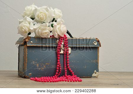 An Old Worn Out Blue Suitcase With A Bunch Of Artificial White Roses And A String Pink Beads