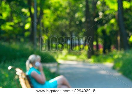 Young Girl Sitting On Bench In City Park And Talking On Phone. Background Is Blurred. Lifestyle Conc