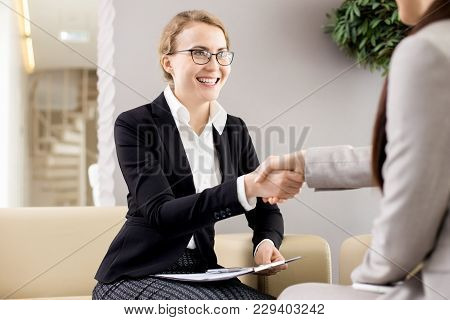Cheerful Young Entrepreneur In Formalwear Shaking Hand Of Business Partner After Successful Completi