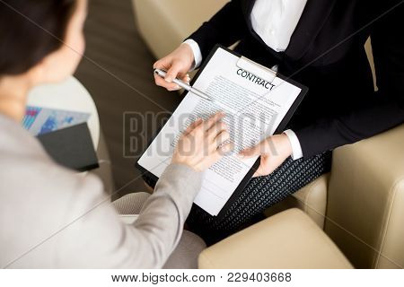 Close-up Shot Of Unrecognizable Businesswoman Studying Contract Before Signing It While Having Negot