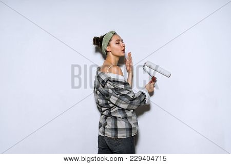 Young Girl In Old Shirt Colors The Wall With A Platen Roller In White, Doing Repairs
