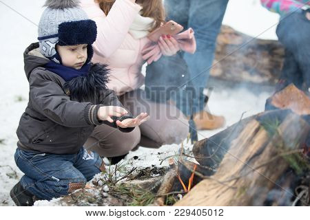 Belarus, Gomel, February 18, 2018. Russian Holiday Seeing Off Winter Maslenitsa.a Boy Is Warming His