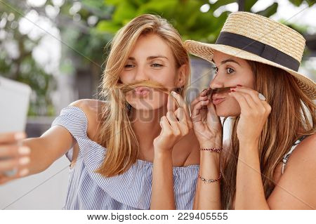 Funny Adorable Women Foolish And Make Grimace, Make Photo Of Themself On Cell Phone, Enjoy Good Rest