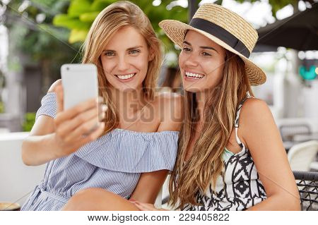 People, Leisure, Lifestyle And Modern Technology Concept. Two Happy Lesbians Have Fun Outdoors. Blon