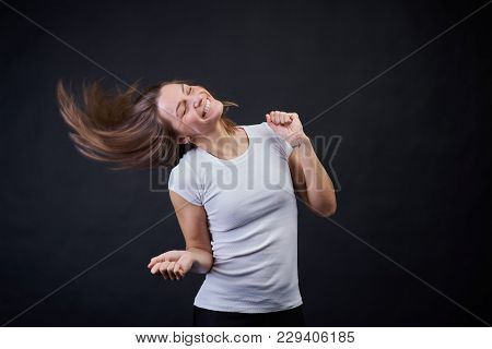 Studio Portrait On A Black Background Of A Young Athletic Girl Dancing And Having Fun. Her Hair Flut