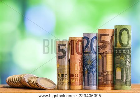 Five, Ten, Twenty, Fifty And One Hundred Euro Rolled Bills Banknotes, With Euro Coins On Ggeen Blurr