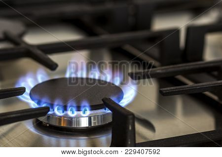 Natural Gas Burning On Kitchen Gas Stove In The Dark. Panel From Steel With A Gas Ring Burner On A B