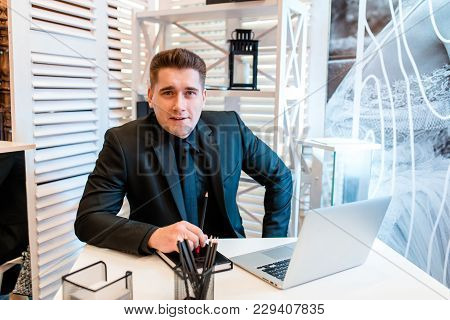 Businessman Working At Laptop In Beautiful Office And Smiling..