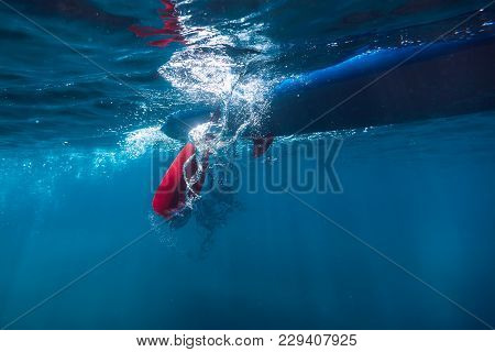 Surfer Riding On Stand Up Paddle Board. Underwater Shot With Paddle And Board In Ocean