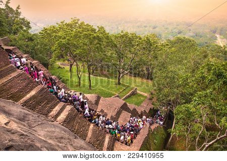 SIGIRIA, SRI LANKA - DEC 26, 2016: A handful of tourists are waiting to climb on Sigiriya rock fortress in Sigiriya on Dec 26, 2016, Sri Lanka. Sigiriya is a UNESCO World Heritage site.