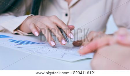 Business Woman Showing Financial Diagram, Graph, Business Charts During Conference Sitting At The Of