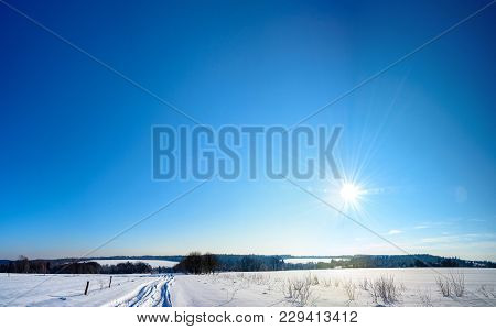 The Bright Sun Goes Down In Winter Over The Ukrainian Countryside With Magnificent Rays