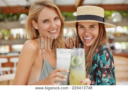 Adorable Cheerful Females Wear Summer Hat, Blouse, Have Shining Broad Smiles, Clink Glasses Of Cockt