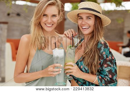 Beautiful Females Stand Close To Each Other, Have Positive Looks, Recreat At Beach Resort, Hold Fres