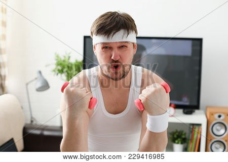 Young Attractive Man Engaged In Fitness At Home Holding Dumbbell In Hand Trying To Fight Excess Weig