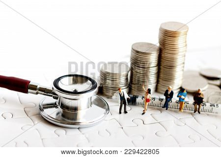 Miniature People Sitting On Syringe Wit Stethoscoper And Stack Of Coins, Business And Health Care Co