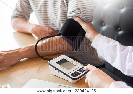 Healthcare, Hospital And Medicine Concept - Doctor And Patient Measuring Blood Pressure By Machine.