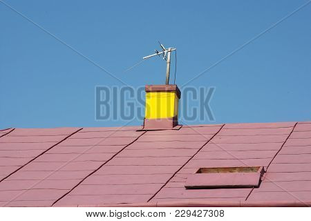 The Roof Of The House With Yellow Chimneys On The Background Of The Sky Blue