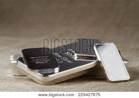 Silver Bullion On A Blurred Background. Silver Cast And Minted Bars Of Different Weights. Selective