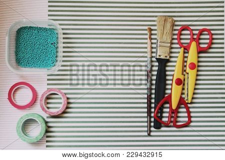 Hobby, creativity, needlework, artisan art. Scissors, brushes, artist accessories, striped backgroun