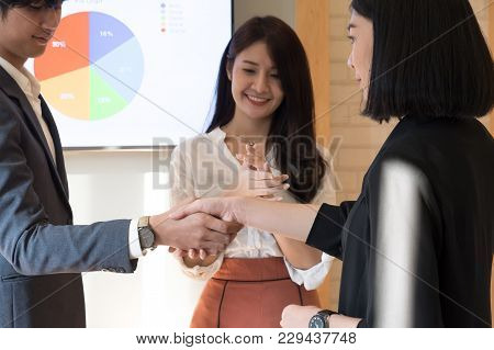 Cheerful Businessman Shaking Hands With Businesswoman While Businesspeople Applauding In The Backgro